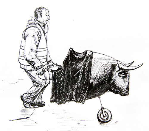 A man pushes a carretón, or cart, a fake bull's head on wheels. During Carnival children play at running from bull's and passing bulls using these contraptions.